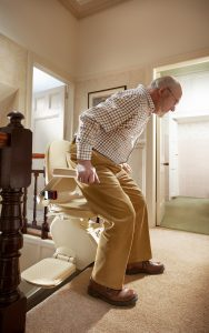 Man getting out of a stairlift at the top of a staircase